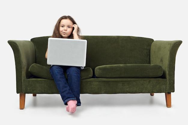 Foto van peinzende schattig meisje met behulp van laptop terwijl huiswerk, hoofd krabben, onzekere twijfelachtige blik