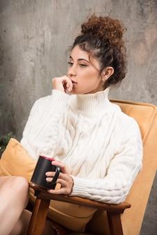 Foto van peinzende vrouw zittend in een comfortabele stoel met een kopje drank