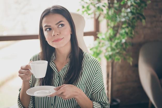 Foto van peinzende zakelijke dame drinkt koffie dromen op kantoor