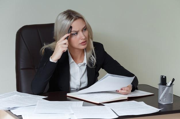 Foto van peinzende zakenvrouw met groot notitieblok in pak aan tafel zitten met documenten