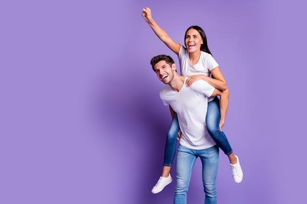 Foto van piggyback vrij schattig paar in spijkerbroek denim wit t-shirt met man met meisje haar hem naar voren te leiden glimlachend toothily geïsoleerde pastelkleur achtergrond violet