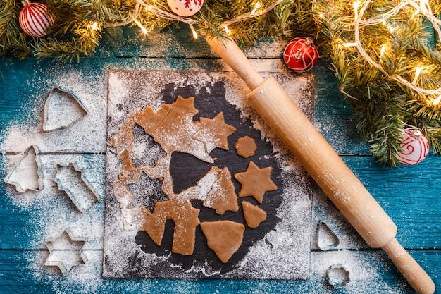 Foto van pijnboomtakken, deeg, koekjesvormen, deegrol