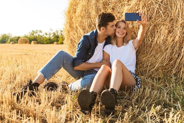 Foto van platteland paar man en vrouw selfie te nemen zittend onder grote hooiberg in gouden veld, tijdens zonnige dag