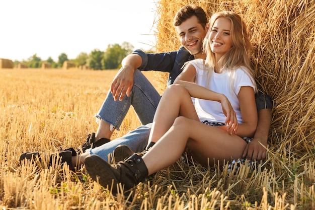 Foto van platteland paar man en vrouw zitten onder grote hooiberg in gouden veld, tijdens zonnige dag