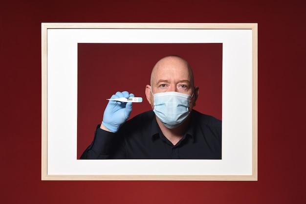 Foto van portret van een man met handschoenen, masker en thermometer op een rode achtergrond