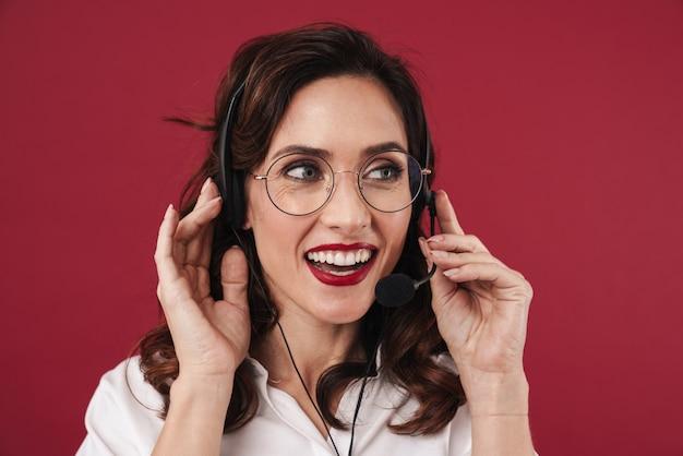 Foto van positief lachende jonge vrouw werken in callcenter geïsoleerd op rode muur praten via mobiele telefoon.