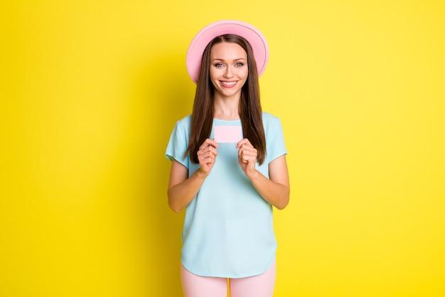 Foto van positief meisje houdt plastic kaart coupon voucher betalen aankoop geld verkoop korting draag roze broek broek geïsoleerd over heldere glans kleur achtergrond