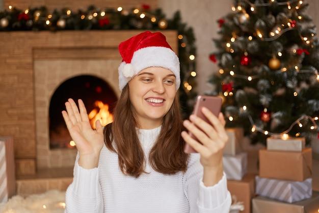 Foto van positief meisje met behulp van haar smartphone leest tekstberichten of kerstkortingen zoeken