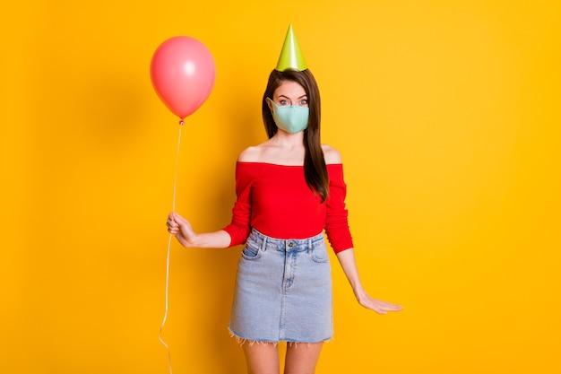 Foto van positief meisje met medisch masker geniet van covid quarantaine verjaardagsfeestje houd ballon draag rode top denim jeans korte minirok kegel geïsoleerd over heldere glans kleur achtergrond