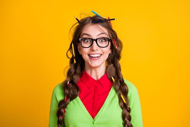 Foto van positief meisje met potloodkapsel verbaasde blik in de camera geïsoleerd glans kleur achtergrond