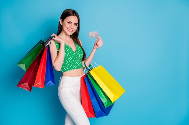 Foto van positief vrolijk meisje houdt veel tassen vast, geniet van betaalaankoop creditcard, draag een witte broek, broek, tanktop geïsoleerd op een blauwe achtergrond