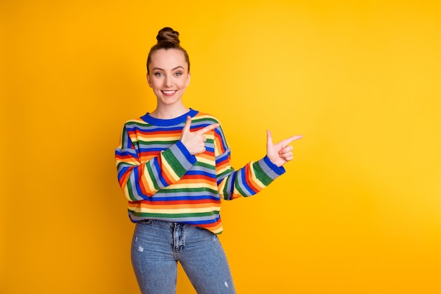 Foto van positief vrolijk meisje promotor punt wijsvinger copyspace beslissen kies adviseren advertenties promotie draag trui geïsoleerd over felle kleur achtergrond