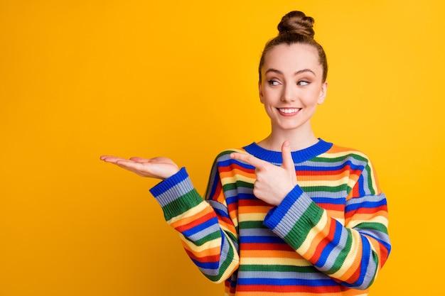 Foto van positief vrolijk meisje promotor punt wijsvinger houd hand copyspace kies keuze beslissen besluit adviseren advies advertenties promo draag trui geïsoleerde felle kleur achtergrond