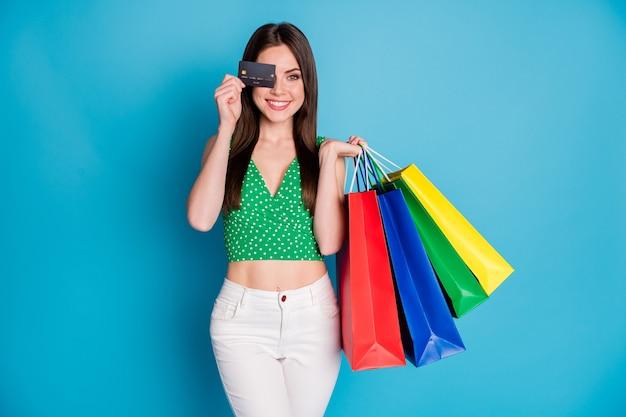 Foto van positief vrolijk meisje sluit dekking oog creditcard geniet van winkelen houd veel tassen dragen witte broek broek groen gestippelde tank-top geïsoleerd over blauwe kleur achtergrond