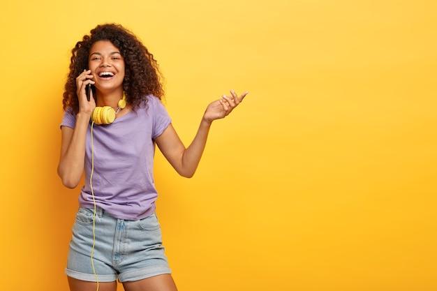 Foto van positieve afro-amerikaanse meisje praat op mobiele telefoon, glimlacht in het algemeen, steekt hand op, deelt indrukken over winkelen, bespreekt laatste modetrends