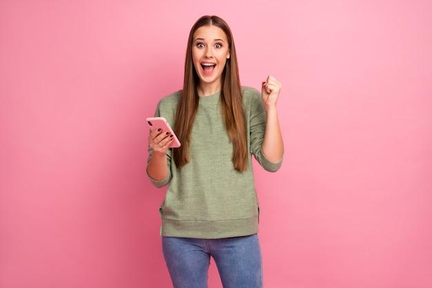 Foto van positieve blogger-gebruiksmartphone heft vuisten op schreeuwen