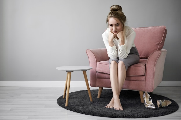 Foto van positieve charmante jonge europese zakenvrouw elegante formele kleding dragen zittend in een stoel met blote voeten op tapijt thuis, mysterieus glimlachend, kin op haar handen rusten