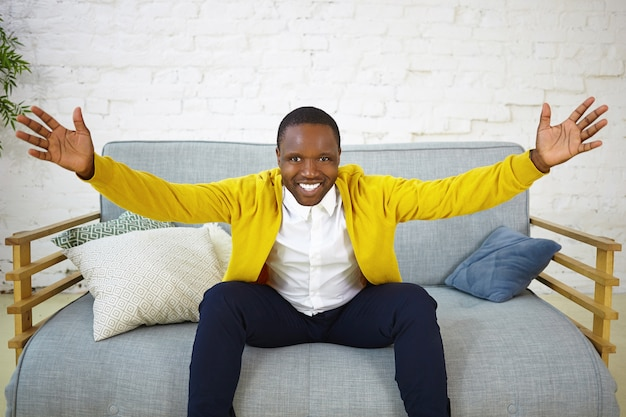 Foto van positieve emotionele jonge afro-amerikaanse man met brede glimlach, handen opsteken alsof ze je willen omhelzen, vriendelijke opgewonden blik hebben, zich verheugen over goed nieuws. menselijke emoties en gevoelens