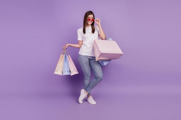 Foto van positieve grappige dame draagt boodschappentassen geïsoleerde violette achtergrond