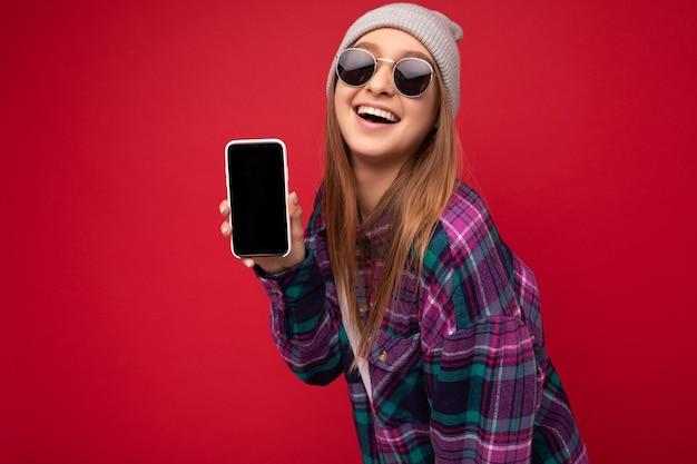 Foto van positieve jonge blonde vrouw, gekleed in stijlvol paars shirt en casual wit t-shirt