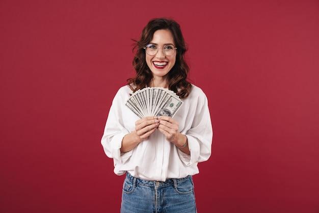 Foto van positieve lachende gelukkige jonge vrouw geïsoleerd op rode muur aanhouden van geld.
