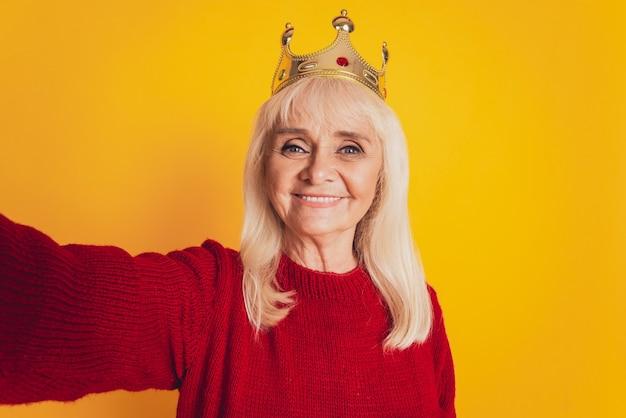 Foto van positieve oude vrouw met gouden kroon maakt selfie