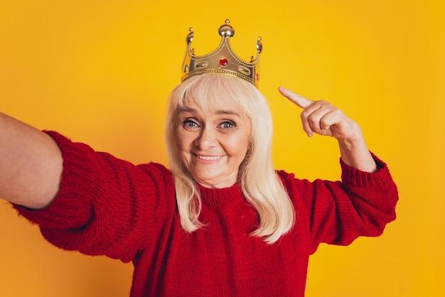 Foto van positieve oude vrouw met puntvinger gouden kroon maakt selfie