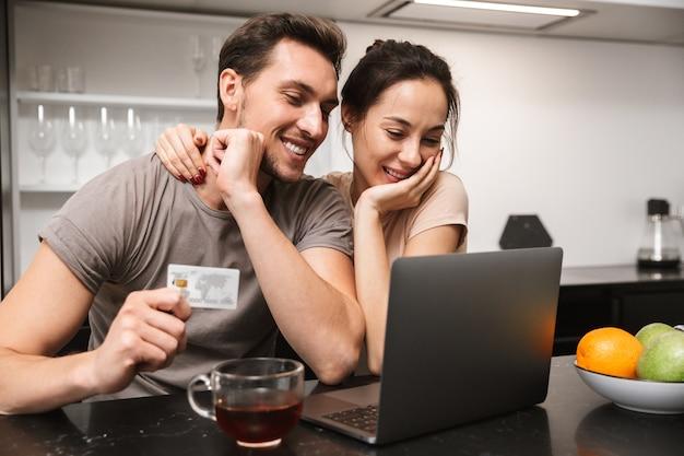Foto van positieve paar man en vrouw met behulp van laptop met creditcard, zittend in de keuken