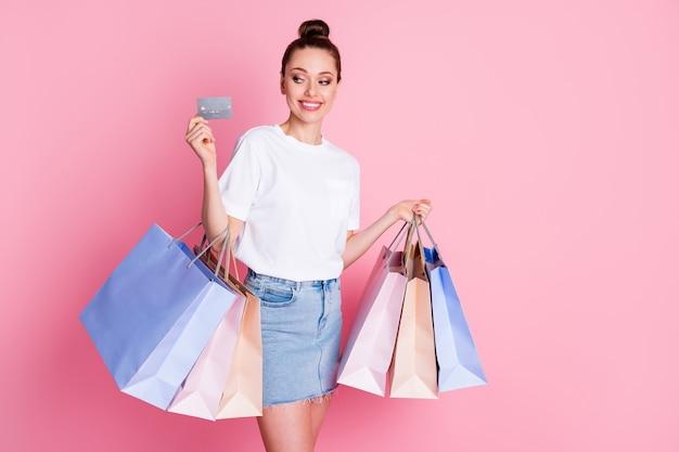 Foto van positieve vrolijke meid-look creditcard geniet van winkelen, houd veel tassen vast
