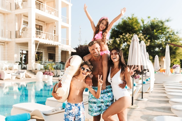 Foto van prachtige europese familie met kinderen rusten in de buurt van luxe zwembad, en plezier maken met rubberen ring buiten hotel