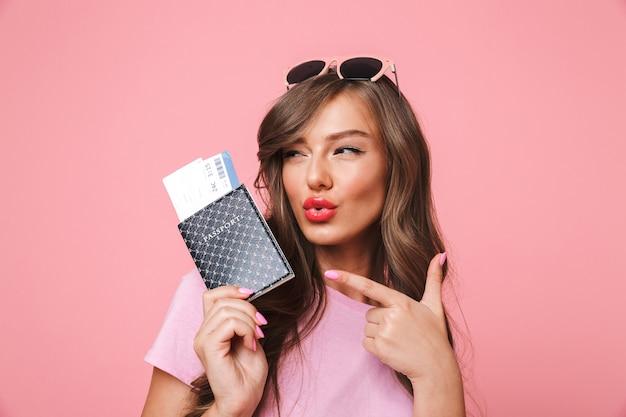 Foto van prachtige glamour vrouw met mooi lang haar wijzende vinger op paspoort en vliegtickets in de hand houden, geïsoleerd op roze achtergrond