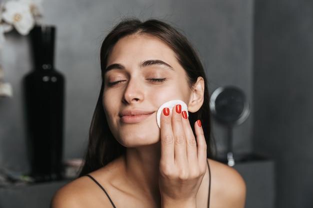 Foto van prachtige vrouw met lang donker haar en een gezonde huid die haar gezicht met wattenschijfje schoonmaken
