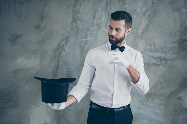 Foto van professionele illusionist die doet alsof hij een spreuk uitspreekt om iets uit zijn cilindrische hoed te halen, geïsoleerd over grijze betonnen muurmuur