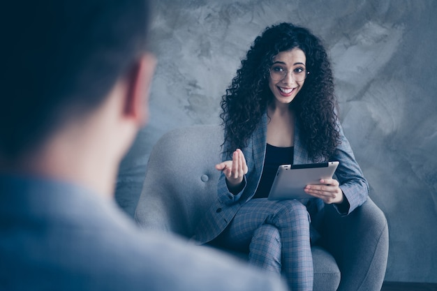Foto van psycholoog meisje zittend in stoel overleg geven over betonnen muur achtergrond