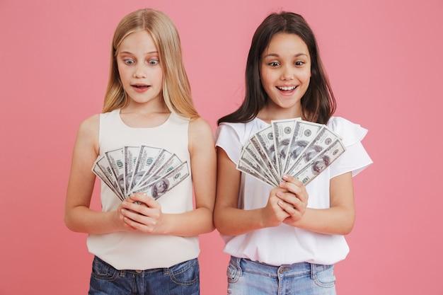 Foto van rijke brunette en blonde meisjes 8-10 die vrijetijdskleding dragen die veel geld in dollarbankbiljetten houden, die over roze achtergrond worden geïsoleerd