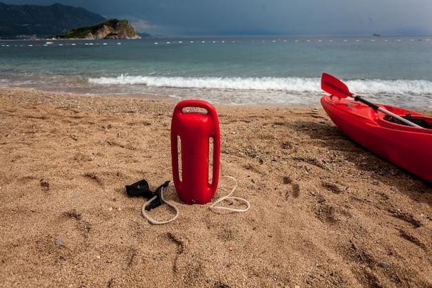 Foto van rode reddingsboei en badmeesterkano op zandig strand bij stormachtige dag