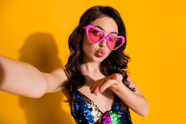 Foto van romantische droom flirt meisje blogger maakt selfie stuur lucht kus hand naar haar volgers draag rok roze hartvorm bril geïsoleerd over heldere glans kleur achtergrond