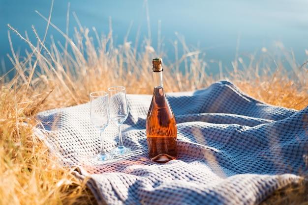 Foto van rose champagne en twee glazen dichtbij zee of oceaan tijdens zonsondergang