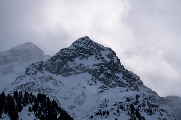 Foto van rotsachtige bergen bedekt met de sneeuw onder een bewolkte hemel en zonlicht