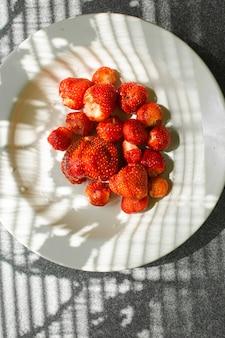 Foto van sappige verse rijpe rode aardbeien in een witte keramische plaat op tafel onder fel zonlicht in een dorp