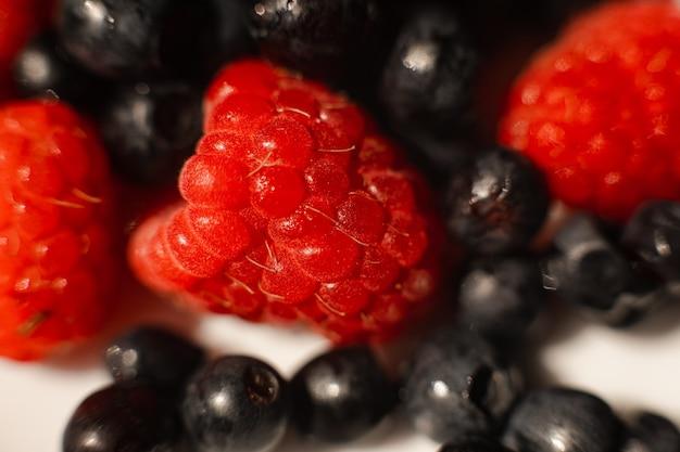 Foto van sappige verse rijpe rode aardbeienbessen in een witte keramische plaat op tafel onder fel zonlicht