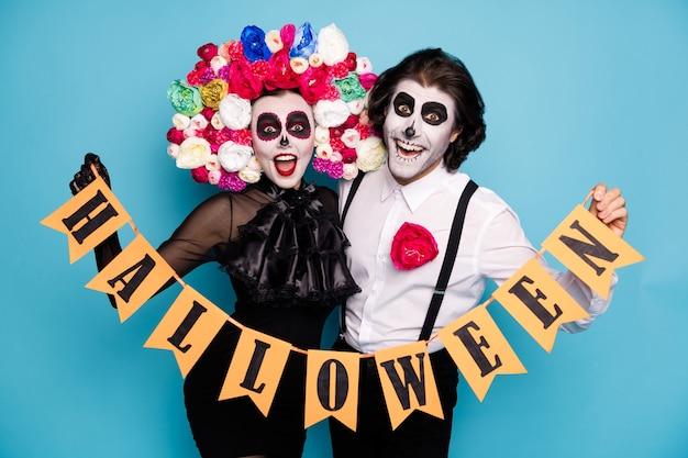 Foto van schattig beangstigend paar man dame knuffelen vasthouden gemarkeerd lint kostuum herfst thema evenement dragen zwarte jurk dood kostuum rozen hoofdband bretels geïsoleerde blauwe kleur achtergrond
