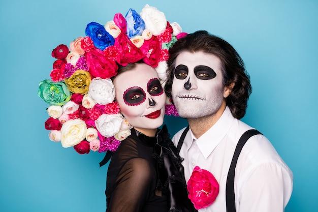 Foto van schattig eng romantisch koppel man dame knuffelen voorbereiden bijwonen ondode bal vriend uitnodiging dragen zwarte jurk dood kostuum rozen hoofdband bretels geïsoleerde blauwe kleur achtergrond
