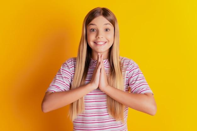 Foto van schattig klein meisje houdt smekende handen geïsoleerd op gele achtergrond