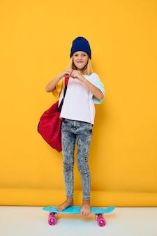 Foto van schattig klein meisje met een skateboard op zijn hoofd gele achtergrond