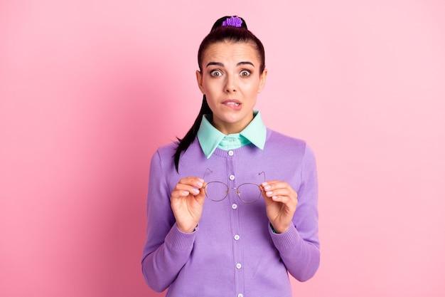 Foto van schattig meisje opstijgen greep specs geschokte blik camera dragen violet vest geïsoleerde roze kleur achtergrond