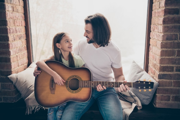 Foto van schattig mooi meisje en knappe jonge papa zitten vensterbank houden akoestische gitaar onderwijs nieuw akkoord weekend tijd huis kamer binnenshuis