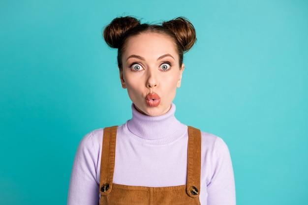 Foto van schattig onder de indruk vroeg zich af kinderachtig twee broodjes kapsel meisje dame afluisteren geheimhouding privé-informatie draag paarse trui bruin fluwelen algehele geïsoleerde turquoise kleur achtergrond