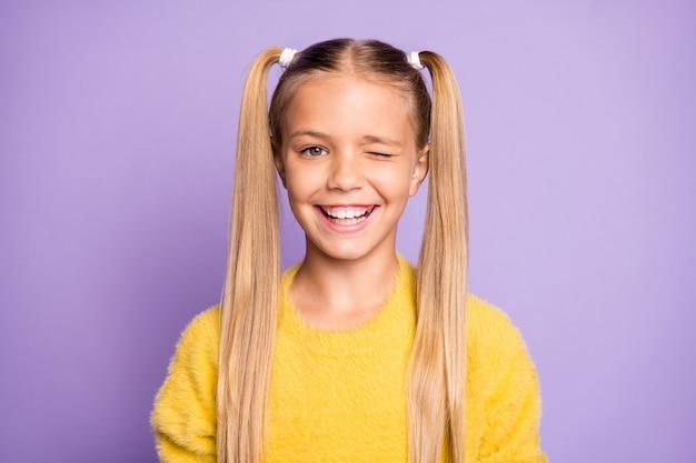Foto van schattig positief vrolijk meisje dat naar je knipoogt om je aandacht te trekken geïsoleerd over pastel violette kleur muur