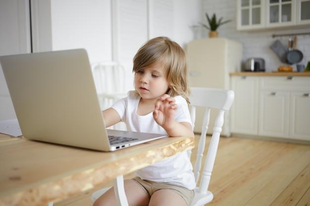 Foto van schattig schattig vrouwelijk kind met mollige wangen met behulp van generieke laptopcomputer, zittend aan tafel in de keuken, surfen op internet, tekenfilms, videoblog kijken of online spelletjes spelen